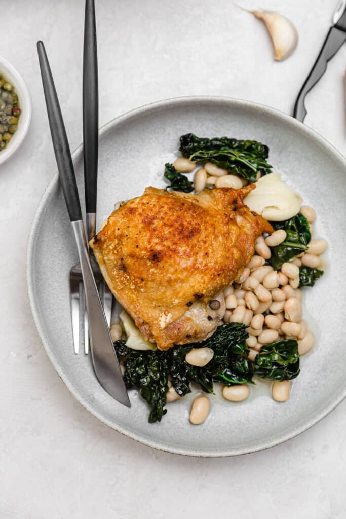 skillet chicken with white beans and kale on a gray plate