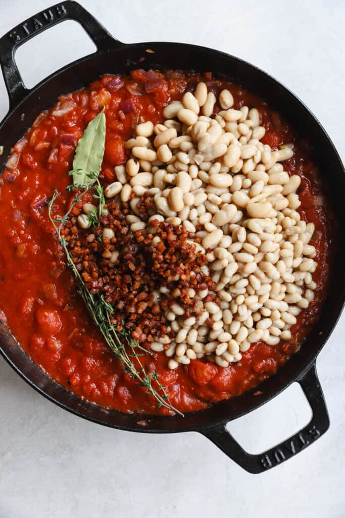canned tomatoes, white beans, pancetta, and fresh herbs in a staub pan