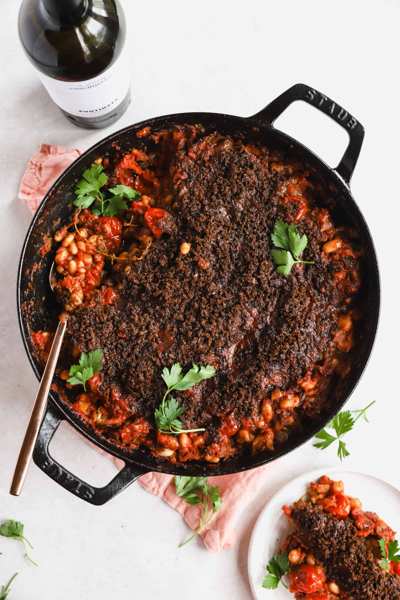 chorizo cassoulet with parsley in a staub skillet