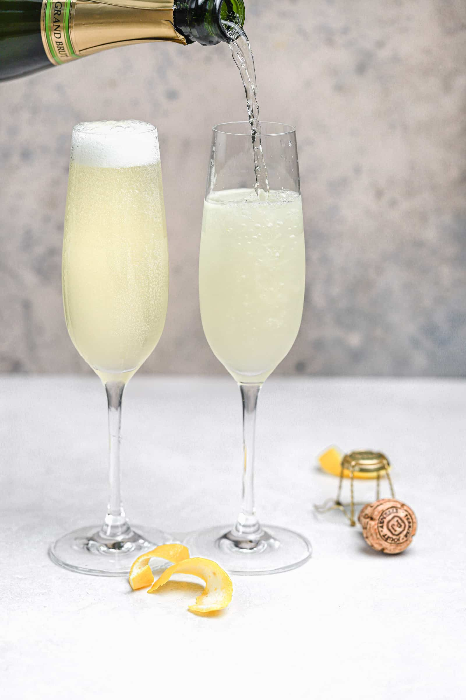 Champagne being poured into flute with gin, lemon juice, and simple syrup