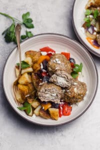 goat cheese stuffed chicken meatballs with roasted veggies and potatoes in a bowl