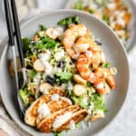 close up of chopped salad with halloumi and roasted shrimp in a gray bowl
