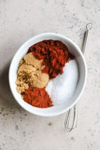 kosher salt, brown sugar, paprika, and cayenne in a white bowl