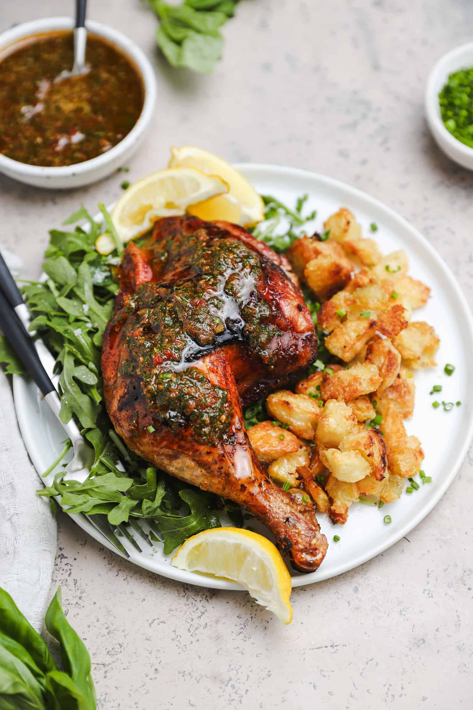 chicken thigh and leg that is topped with sun dried tomato herb oil, served on a white plate with arugula, crispy potatoes, and lemon wedges