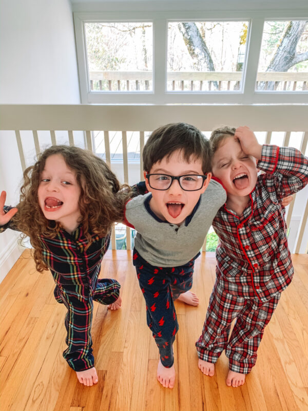 three young children making funny faces standing next to a window