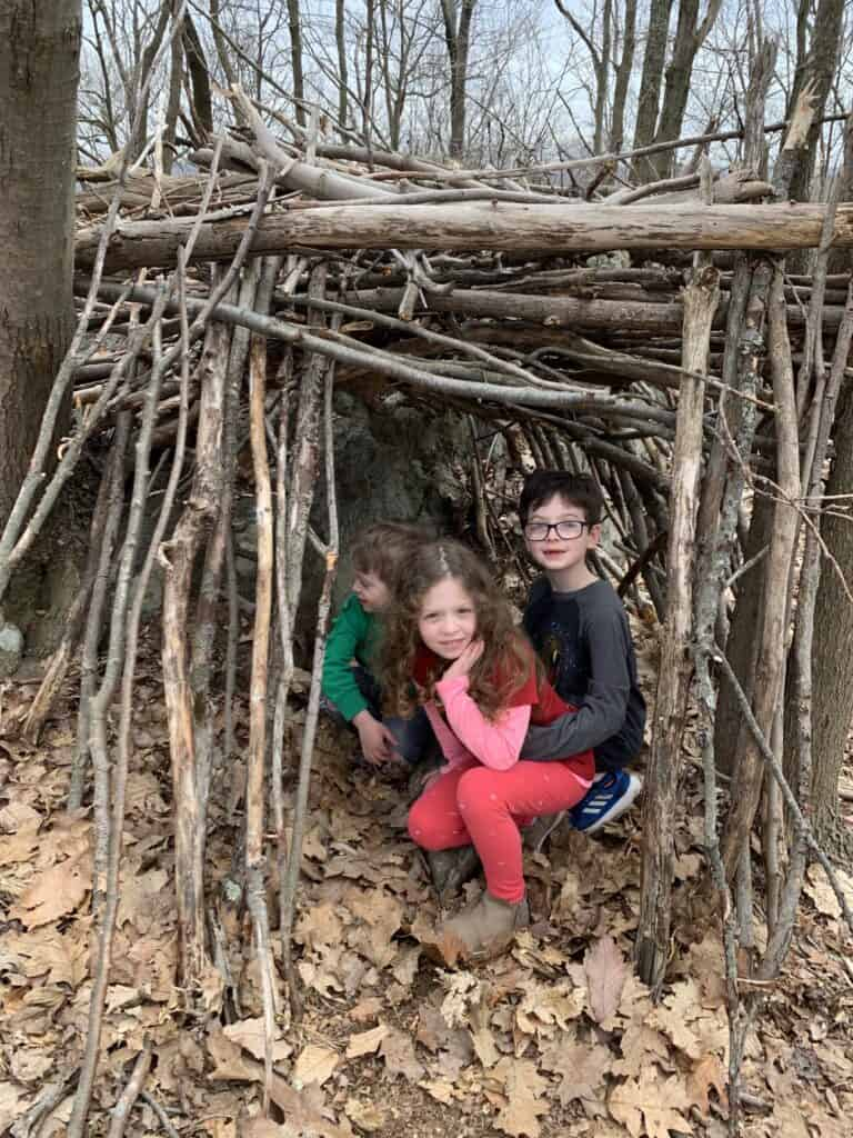 Ari\'s three kids in a fort made out of sticks.