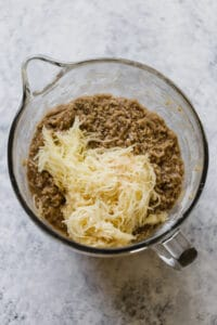 grated apple added to cinnamon apple cake batter in a large mixing bowl