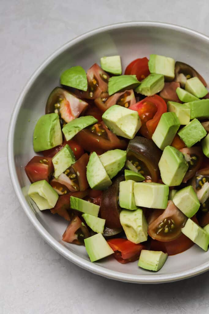 avocado and heirloom tomato chunks in a grey bowl