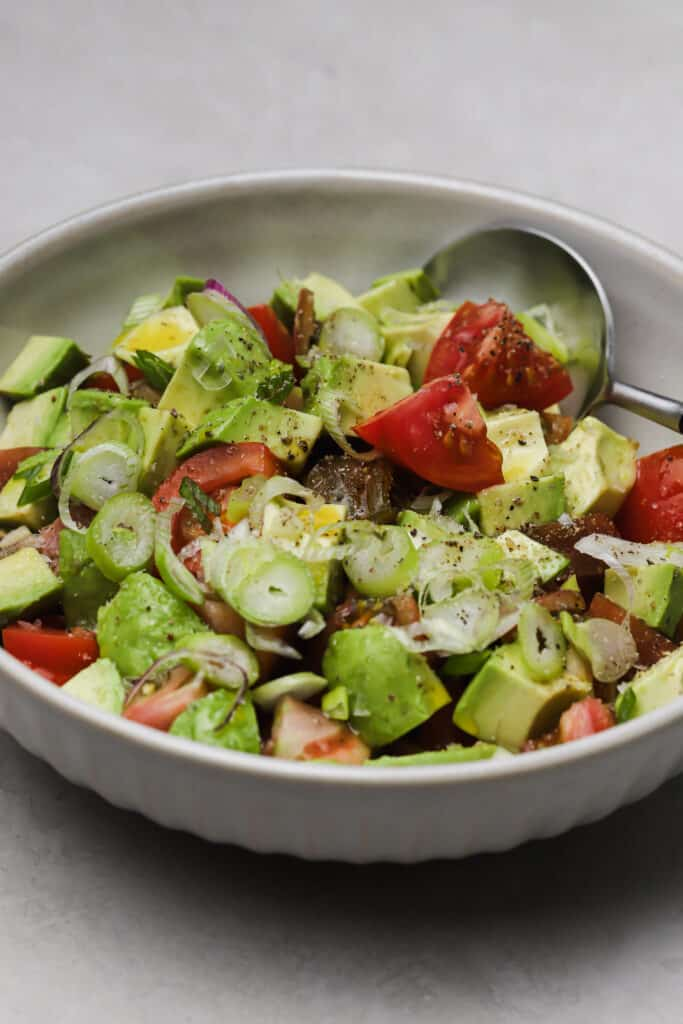summer avocado salad with tomatoes and scallions in a large bowl