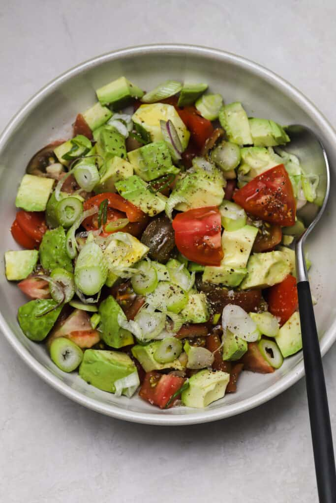 tomato salad with ripe avocados and scallions in a serving bowl