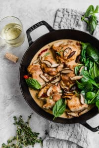 sun dried tomatoes with shiitake mushrooms and spinach in a cast iron skillet