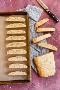 slicing and baking biscotti on a baking sheet