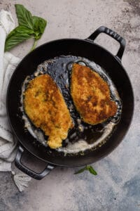 chicken breasts pan fried in a cast iron skillet