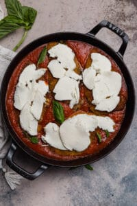 chicken cutlets with fresh mozzarella in a cast iron skillet with marinara sauce