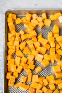 raw butternut squash on a baking sheet with olive oil salt and pepper