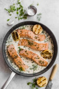 pan seared salmon in a large skillet with coconut milk and mascarpone cream sauce