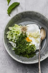 ingredients for herbed yogurt sauce in a dark gray bowl with a spoon