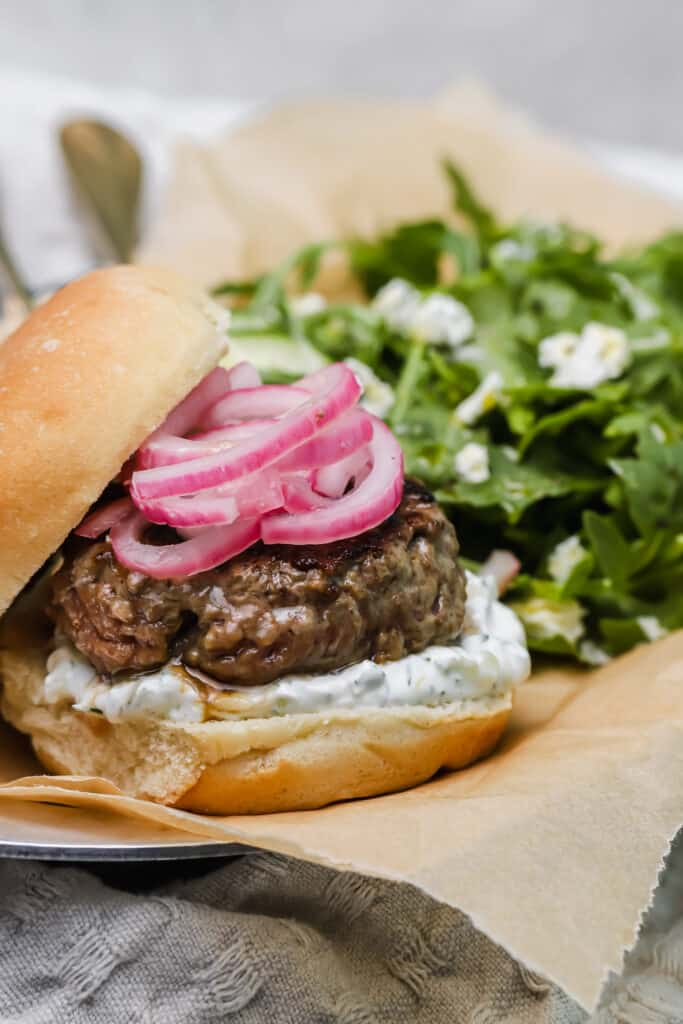 homemade lamb burgers with pickled red onions on a parchment lined plate with an arugula salad in the back