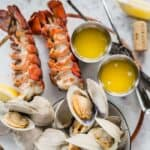 grilled clams and lobster tails on a white platter with butter and lemon wedges