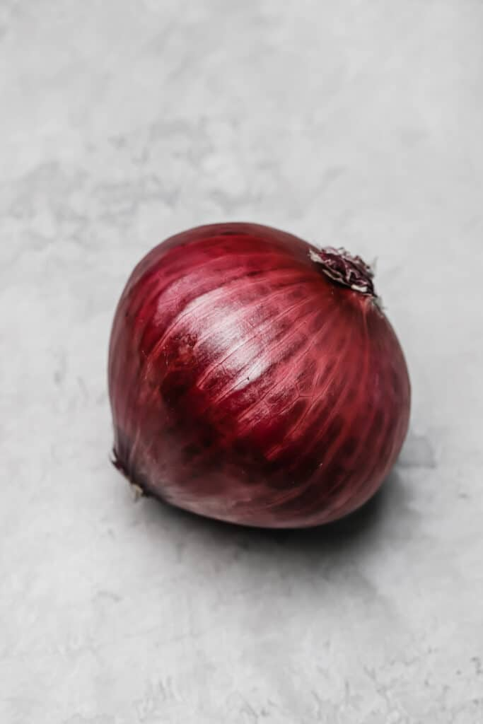 whole red onion on a cement back drop