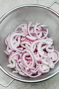sliced red onions in a colander