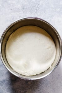 dough for focaccia that has risen in a stainless steel mixing bowl