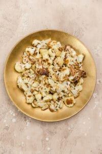 roasted cauliflower florets in a large gold bowl