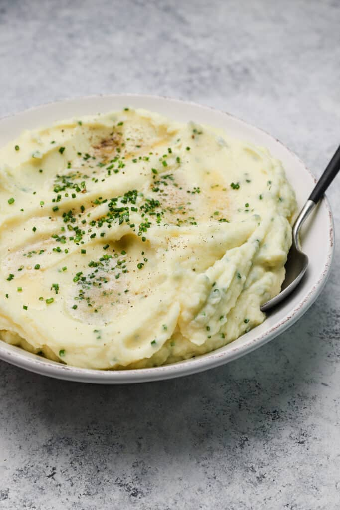 sour cream mashed potatoes with melted brown butter and fresh chives in a white bowl