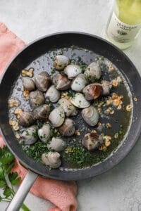 clams in a skillet with garlic, parsley, and white wine