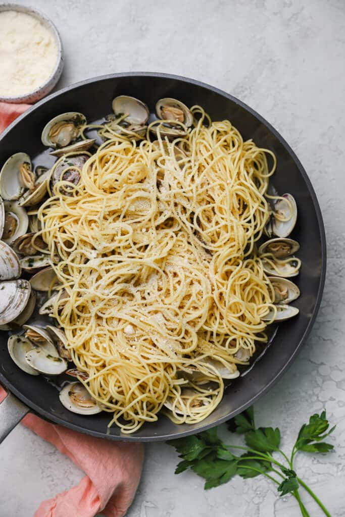 spaghetti on top of cooked clams in a skillet