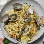 spaghetti with clams and white wine sauce on a plate with parsley and lemon wedges