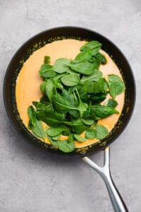 baby spinach in a skillet with homemade thai curry sauce