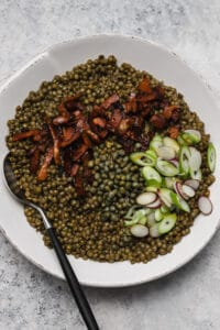 cooked lentils with bacon, scallions, and capers in a large bowl