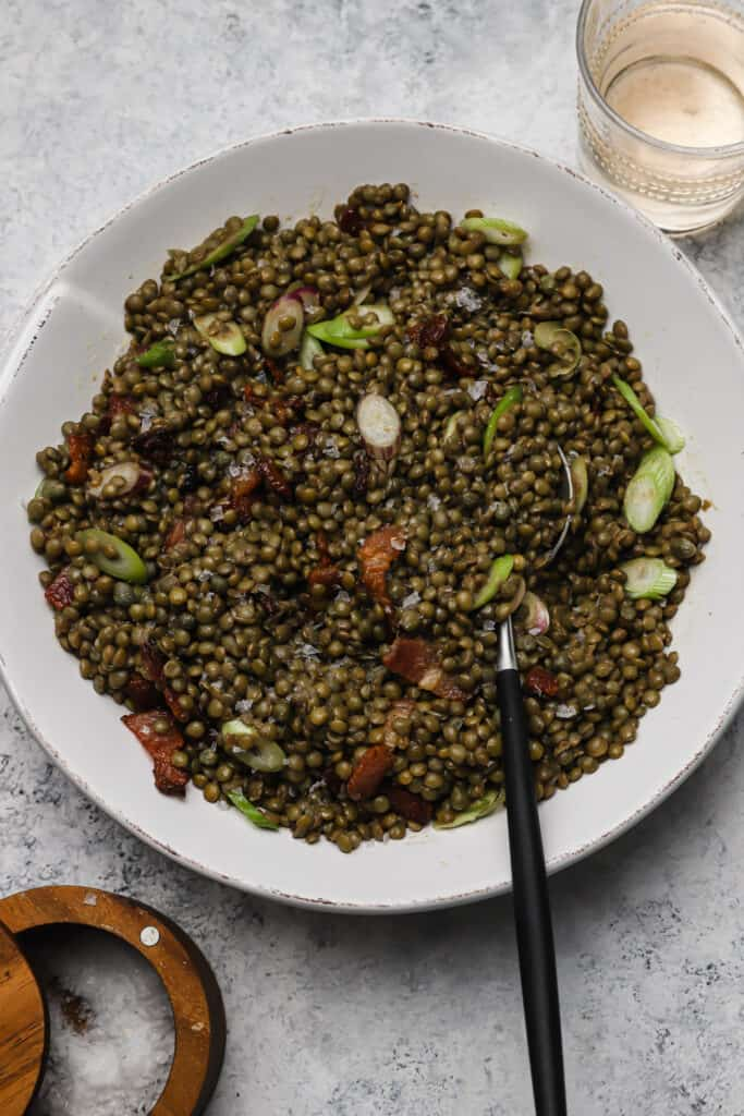green lentil salad with scallions, bacon, and capers in a bowl with serving spoon