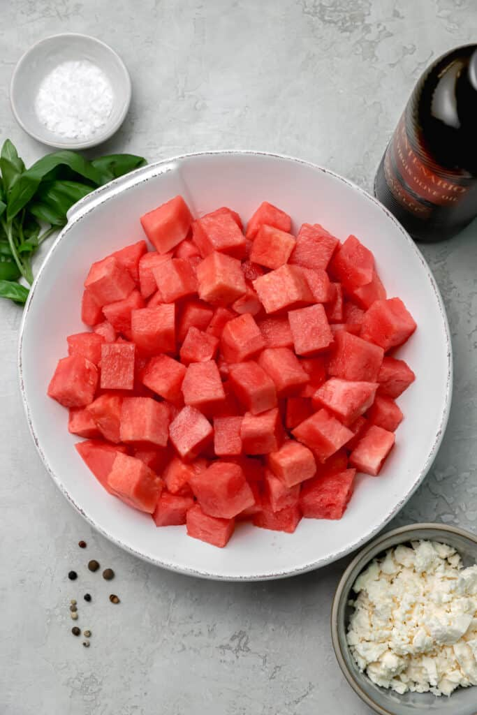 cubed watermelon in a bowl with feta and basil on the side