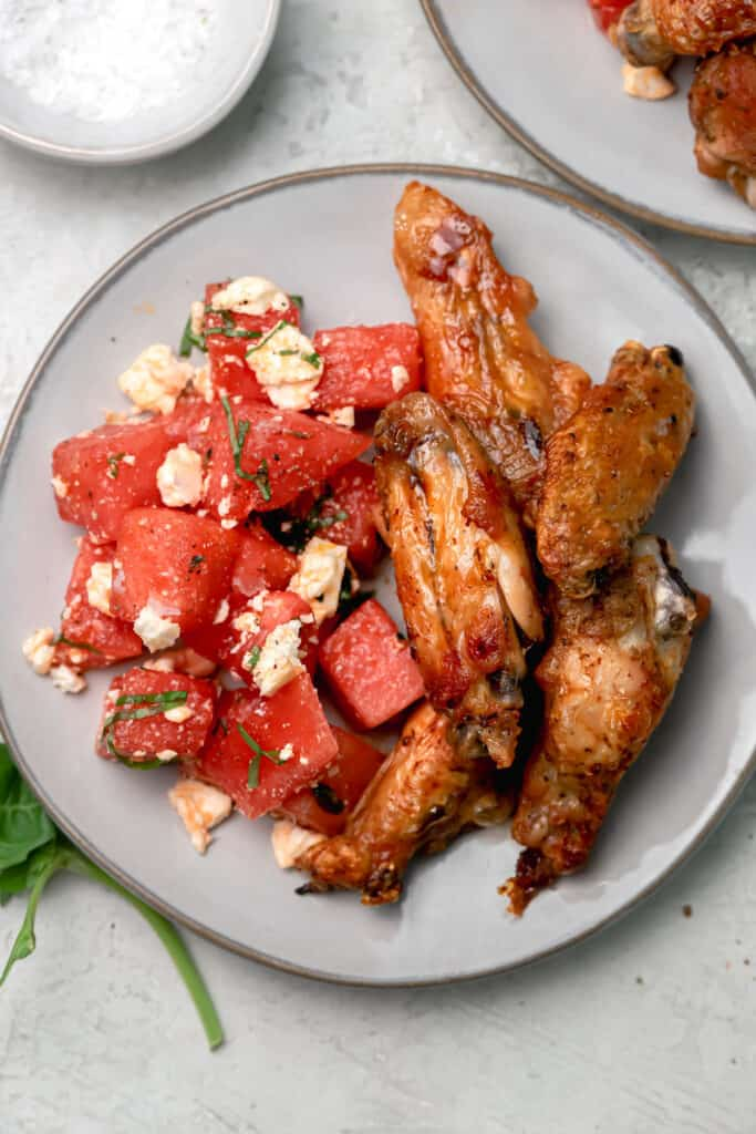 watermelon feta salad with basil and grilled chicken wings on a gray plate