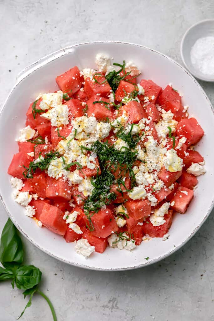 ingredients for watermelon, feta, basil salad in a large bowl