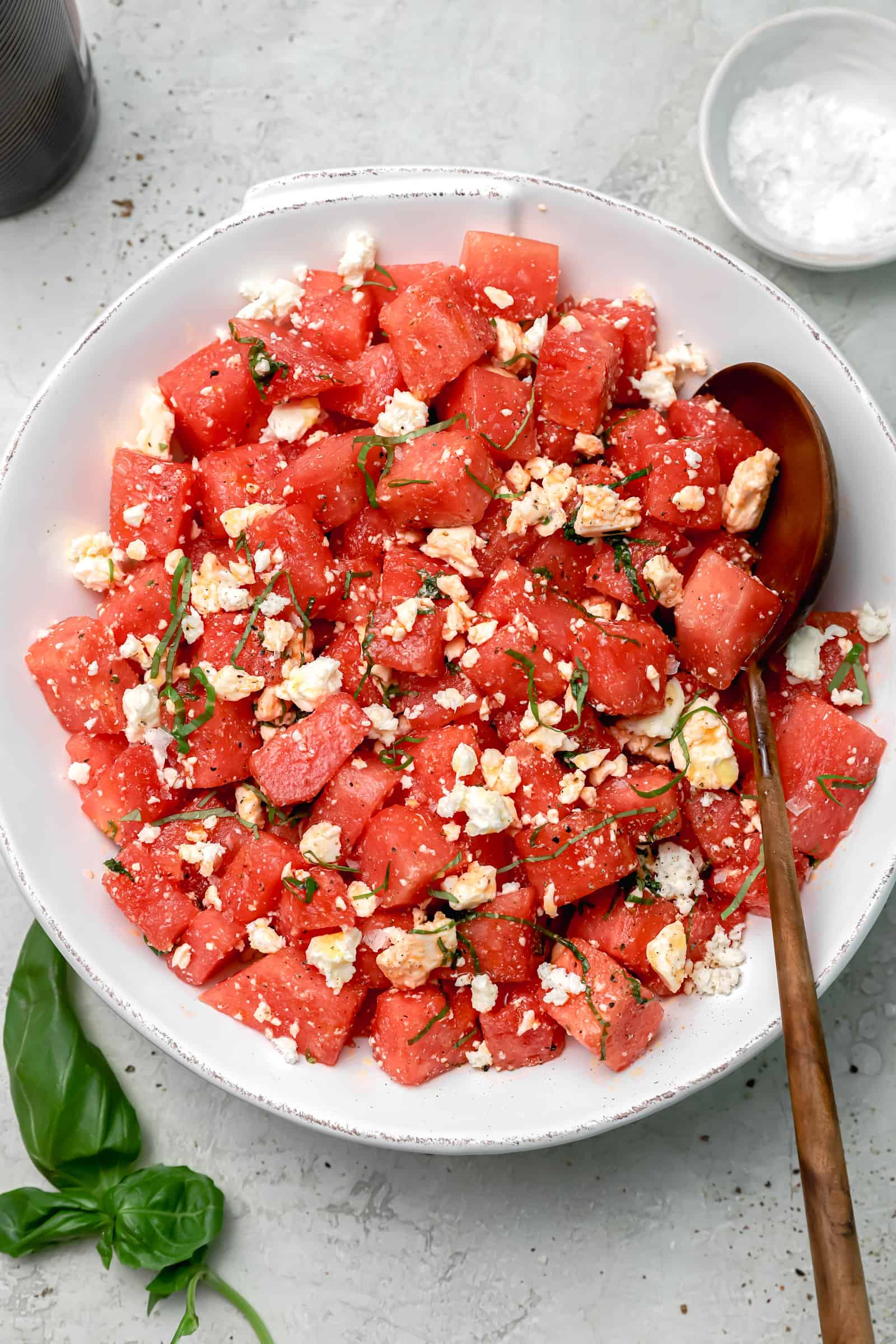 watermelon salad with feta, basil, and flaky sea salt in a large white bowl with brown serving spoon