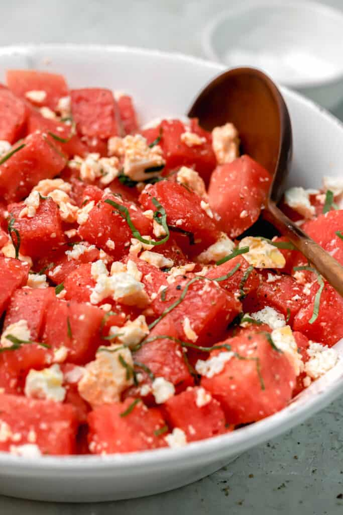 watermelon salad with feta and basil in a white bowl with a wood serving spoon
