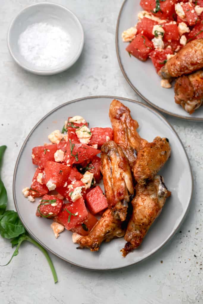 roasted chicken wings with watermelon feta salad on a gray plate