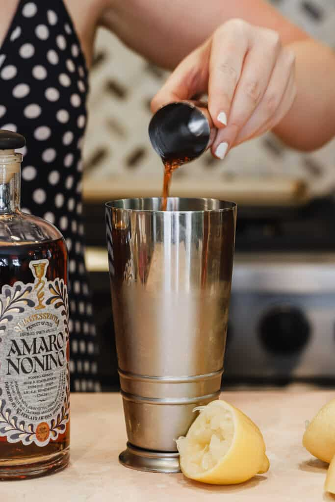 Amaro nonino being poured into cocktail shaker