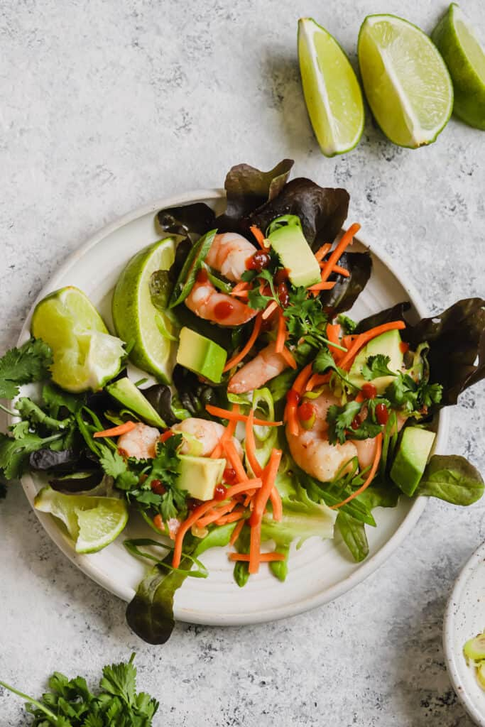 Asian shrimp lettuce wraps on a plate with lime wedges