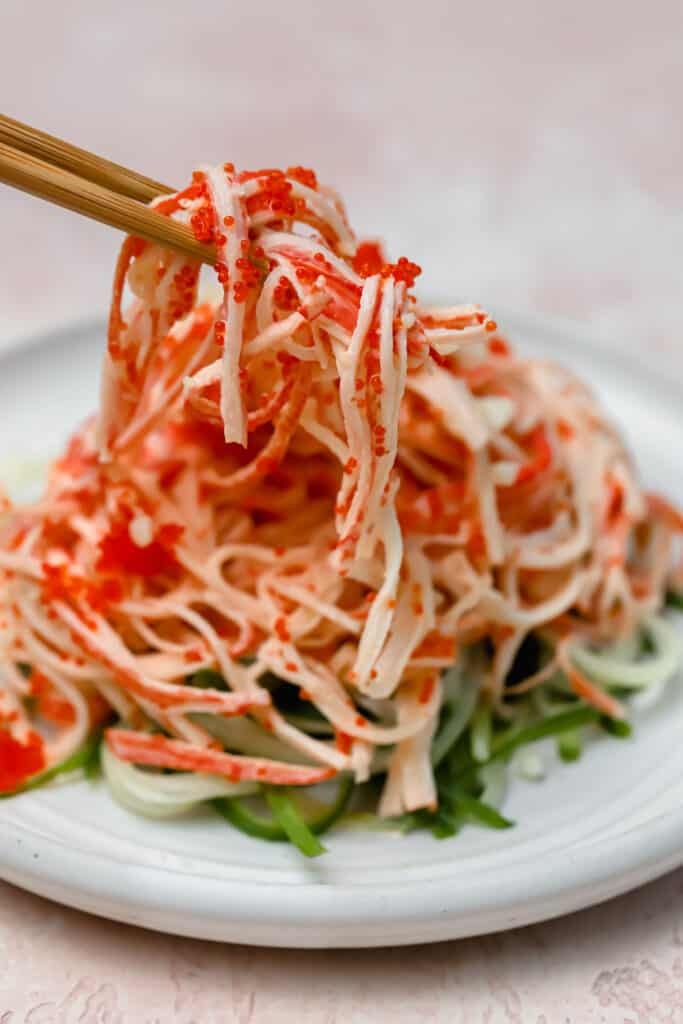 Chopsticks picking up spicy kani salad from a plate