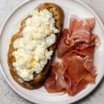 Fresh ricotta cheese served on bread with prosciutto on the side