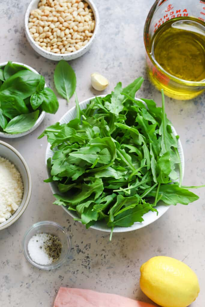 Ingredients for arugula pesto on a board