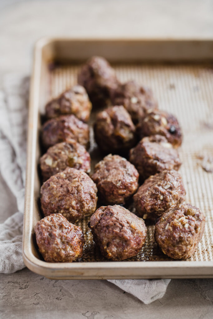 cooked middle eastern lamb meatballs on a baking sheet