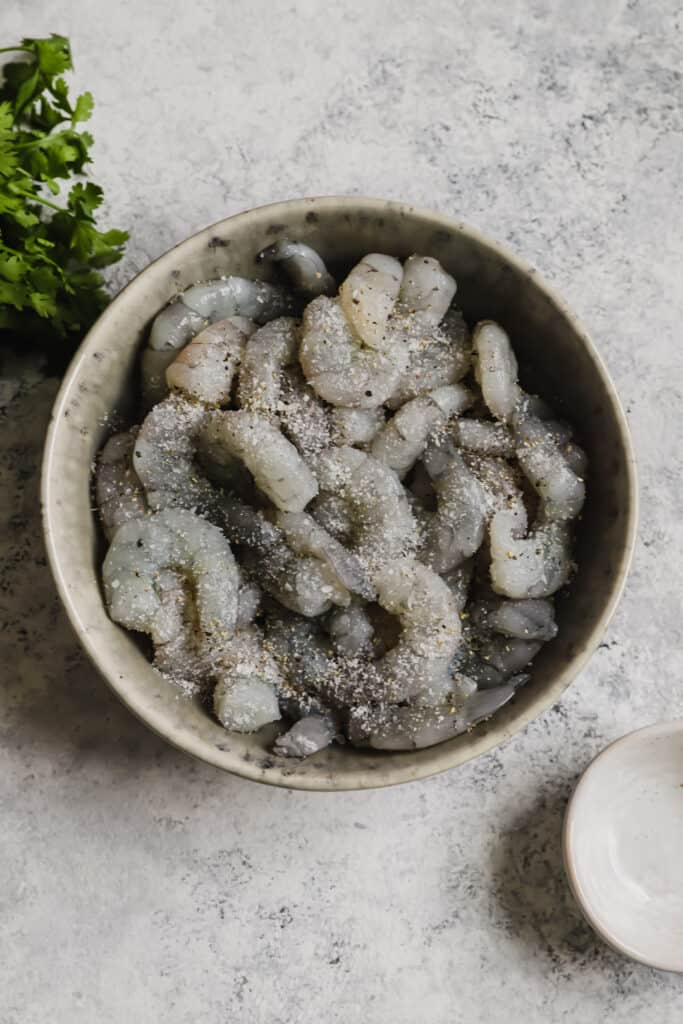 Large peeled and deveined shrimp in a gray bowl