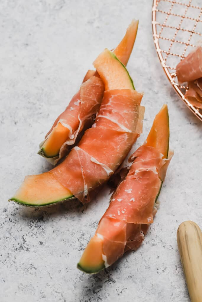 Prosciutto and melon with flaky sea salt on a board