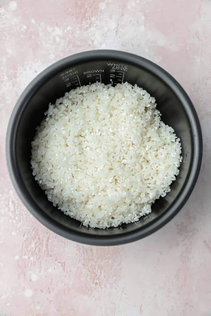 Rinsed rice in a rice cooker bowl