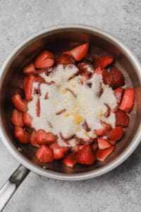 Strawberries in a sauce pan with sugar and lemon zest